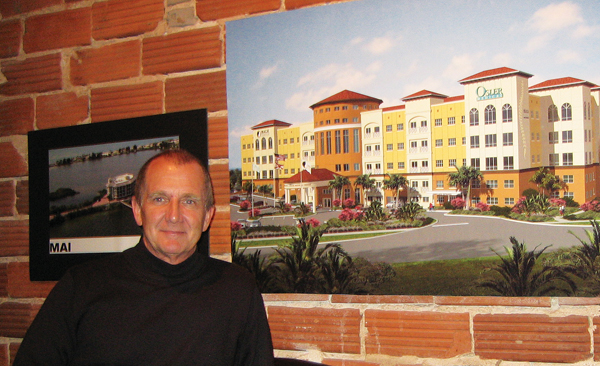 DAVE MENZEL, President of MAI Design Build, with a rendering of the Crane Creek Medical Center. Below, the 210,000 square foot medical structure under construction.